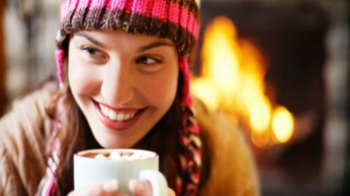 girl-drinking-cocoa-next-to-fireplace